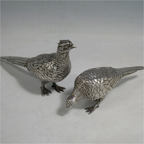 A cast Sterling Silver pair of pheasants, showing a male and female bird in realistic traditional poses, finely detailed with hand-chased bodies and tail feathers. Made by Robert Glover of London in 1973. The dimensions of these fine hand-made sterling silver pheasants are length of male bird 17 cms (6.75 inches), height 8 cms (3 inches), and they weigh a total approx. 310g (10 troy ounces).