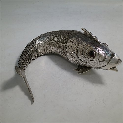 A rare Antique Victorian Silver large articulated fish, with hand engraved and chased body having  articulated scales, a hinged mouth and face with cabochon garnet eyes, with a tail fin, dorsal fin, and sitting on two lower pelvic fins. Made in ca. 1890 in mainland Continental Europe (possibly Spain). The dimension of this fine hand-made antique silver fish model are length 30.5 cms (12 inches), and it weighs approx. 283g (9 troy ounces).