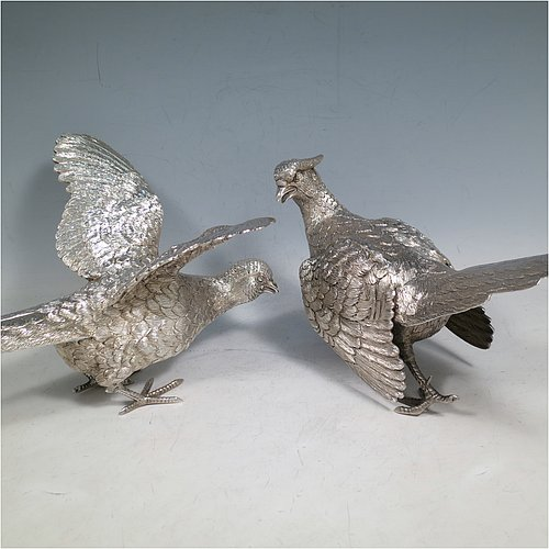 A Sterling Silver large pair of cast pheasants, showing a male and female bird in realistic traditional poses, finely detailed with hand-chased bodies and tail feathers. Made by C. J. Vanders of London in 2000. The dimensions of these fine hand-made sterling silver pheasants are length of male bird 28 cms (11 inches), height 17 cms (6.75 inches), and they weigh a total approx. 1,945g (63 troy ounces).