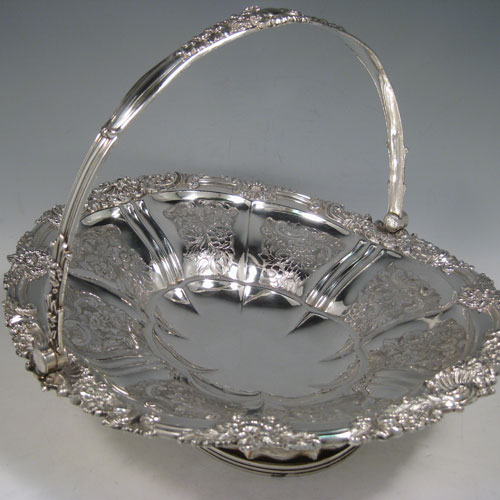 Antique Georgian Old Sheffield plated basket, having an oval body with hand-chased floral decoration in panels, a cast shell and floral border, a hinged swing handle, and all sitting on a pedestal foot. Made in ca. 1825. The dimensions of this fine hand-made Old Sheffield plated basket are height including handle 24 cms (9.5 inches), length 33 cms (13 inches), and width 30.5 cms (12 inches).