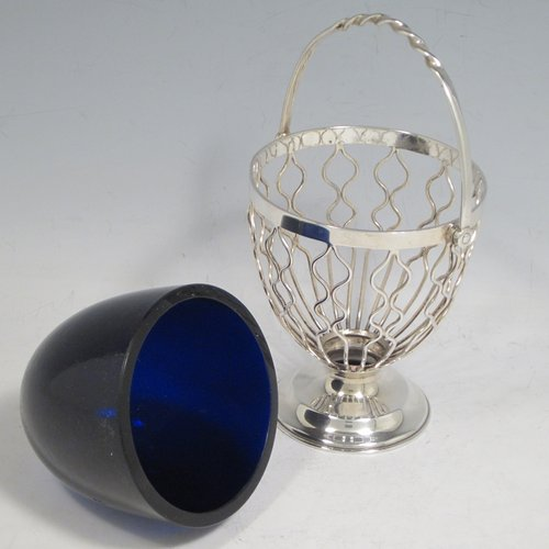 Antique Edwardian sterling silver sweet-meat basket, having a round tapering wire-work body, a  hinged and twisted swing handle, sitting on a plain round pedestal foot, and with an original blue-glass liner. Made by Hukin & Heath of Birmingham in 1902. The dimensions of this fine hand-made silver sweet-meat basket are height inc. handle 15 cms (6 inches), diameter at lip 8.5 cms (3.3 inches), and it weighs approx. 128g (4 troy ounces).