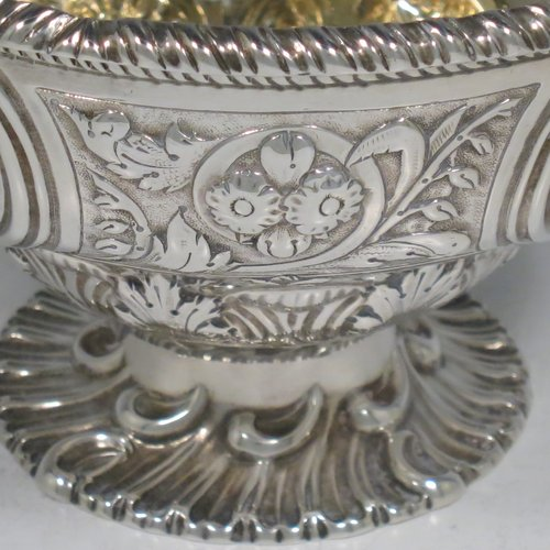 An Antique Victorian Sterling Silver sweet-meat basket, having a round baluster body with gold-gilt interior and an applied gadroon border, with hand-chased floral decoration between four round vacant cartouches, a hinged and florally chased swing handle, and all sitting on a swirl-fluted pedestal foot. Made by Martin and Hall of London in 1871. The dimensions of this fine hand-made antique silver basket are height 15 cms (6 inches), diameter 12.5 cms (5 inches), and it weighs approx. 224g (7.2 troy ounces).