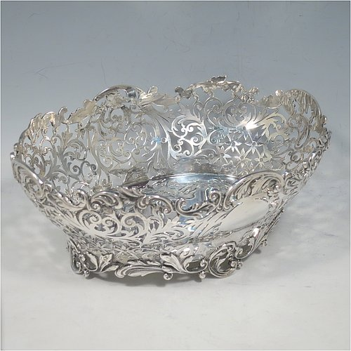 An Antique Victorian Sterling Silver table basket, having an oval hand-pierced body with very pretty floral decoration, with cast floral & scroll  borders, and sitting on four cast floral and scroll feet. Made by James Dixon & Sons of Sheffield in 1901. The dimensions of this fine hand-made antique silver basket are length 21 cms (8.25 inches), width 16 cms (6.25 inches), height 8 cms (3.25 inches), and it weighs approx. 356g (11.5 troy ounces).