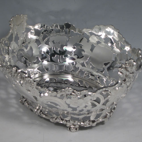 Antique Victorian sterling silver table basket, having an oval hand-pierced and engraved body with floral decoration, with cast floral borders, and sitting on four cast floral feet. Made by D. & J. Wellby of London in 1901. The dimensions of this fine hand-made silver basket are length 18 cms (7 inches), width 16 cms (6.25 inches), height 9 cms (3.5 inches), and it weighs approx. 336g (10.8 troy ounces).