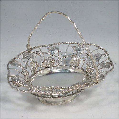 An Antique Georgian Sterling Silver sweet-meat basket with swing-handle, having wire-work decoration with applied grape-vines and leaves, a shaped rope-twist border, a hinged twisted handle, and all sitting on a plain collet foot. Made by Edward Aldridge of London in 1760. The dimensions of this fine hand-made antique silver sweetmeat basket are length 16 cms (6.3 inches), width 13 cms (5 inches), height 13 cms (5 inches), and it weighs approx. 155g (5 troy ounces).