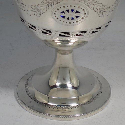 An Antique Edwardian Sterling Silver sweet-meat basket, having a round body with tapering sides all hand-engraved and hand-pierced with neoclassical style decoration, a hinged swing handle with applied bead-work, sitting on a round pedestal foot, and with an original blue-glass liner. Made by Thomas Bradbury of London in 1902. The dimensions of this fine hand-made antique silver sweet-meat basket are height inc. handle 16 cms (6.25 inches), diameter at lip 8.5 cms (3.3 inches), and it weighs approx. 140g (4.5 troy ounces).