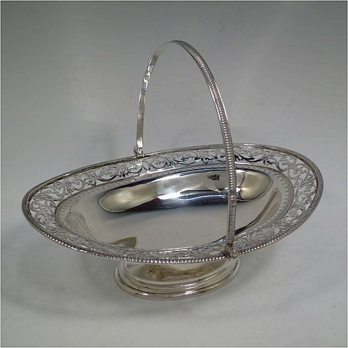 A very pretty Antique Victorian Sterling Silver basket, having an oval body with an applied gadroon border, all hand-pierced with floral and scroll decoration, a hinged swing handle, and all sitting on an oval stepped pedestal foot. Made by J.H. and H. Barraclough of London in 1899. The dimensions of this fine hand-made antique silver basket are height 21 cms (8.25 inches), length 26.5 cms (10.5 inches), width 20 cms (8 inches), and it weighs approx. 548g (17.7 troy ounces).