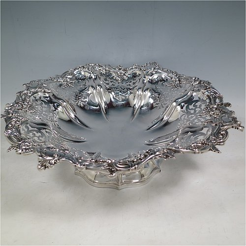 An Antique early Victorian large Sterling Silver table basket, having a round body with hand-pierced floral decoration within melon fluted panels, an applied cast floral and scroll border, and sitting on a melon fluted pedestal foot. Made by the Barnard Brothers of London in 1845. The dimensions of this fine hand-made antique silver basket are diameter 36 cms (14.25 inches), height 11 cms (4.25 inches), and it weighs approx. 1,082g (35 troy ounces).