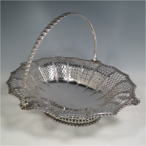 An Antique Georgian Sterling Silver basket, having an oval body with an applied shaped gadroon border, with hand-pierced panels separated by bands of bead-work, a hinged swing handle, and all sitting on a a matching pierced foot. Made by Edward Aldridge of London in 1767. The dimensions of this fine hand-made antique silver basket are height 25 cms (9.75 inches), length 37 cms (14.5 inches), width 31 cms (12.25 inches), and it weighs approx. 900g (29 troy ounces).