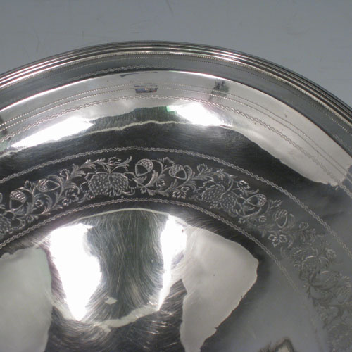 Antique Georgian sterling silver basket, having an oval body with an applied reeded edge, with a band of hand-engraved floral work and acorns, a hinged and reeded swing handle, all sitting on a collet foot. Made in London in 1800. The dimensions of this hand-made silver basket are height 27 cms (10.5 inches), length 35.5 cms (14 inches), width 23.5 cms (9.5 inches), and it weighs approx. 687g (22 troy ounces). Please note that although the hallmarks are rubbed the date letter E is evident.