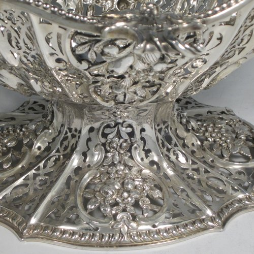 Antique Victorian large sterling silver table basket, in an asymmetrical Art Nouveau style, having an oval hand-pierced body with hand-chased floral decoration, with cast floral and bead-edged borders, and sitting on a matching pedestal foot. Made by Martin Hall & Co., of Sheffield in 1892. The dimensions of this fine hand-made silver basket are length 27.5 cms (10.75 inches), width 23 cms (9 inches), height 21.5 cms (8.5 inches), and it weighs approx. 1,100g (35.5 troy ounces).
