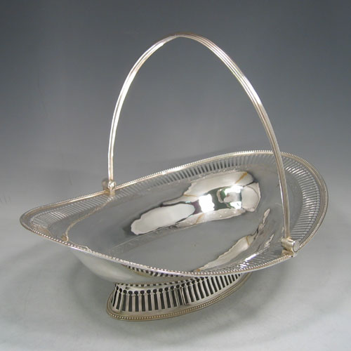 Antique Georgian sterling silver basket, having an oval body with an applied bead edge, a hand-pierced border, with bands of hand-engraved floral work, a hinged and reeded swing handle, all sitting on a hand-pierced collet foot. Made by John Deaken of London in 1777. Height 25.5 cms (10 inches), length 34 cms (13.5 inches), width 25 cms (10 inches). Weight approx. 722g (23.3 troy ounces).