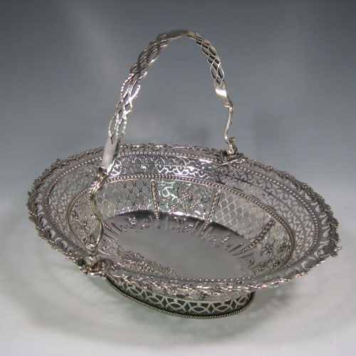 Antique Georgian sterling silver hand-pierced basket with swing-handle, having bands of floral piercing divided by hand-chased bead-work, an applied cast floral border, a cast floral swing-handle, and sitting on a pierced collet foot with rope-twist border. Made by Richard Mills of London in 1772. The dimensions of this fine hand-made silver basket are length 30.5 cms (12 inches), width 27.5 cms (10.75 inches), height 28 cms (11 inches), and it weighs approx. 937g (30 troy ounces).