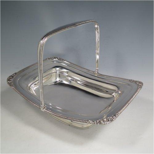 An Antique Edwardian Sterling Silver basket, having a rectangular body, with an applied gadroon and shell border, a hinged and swing handle with gadroon edges, all sitting on a plain pedestal foot. Made by the Barnard Brothers of London in 1903. The dimensions of this fine hand-made silver basket are height 21 cms (8.25 inches), length 27.5 cms (10.75 inches), width 20.5 cms (8 inches), and it weighs approx. 701g (22.6 troy ounces).