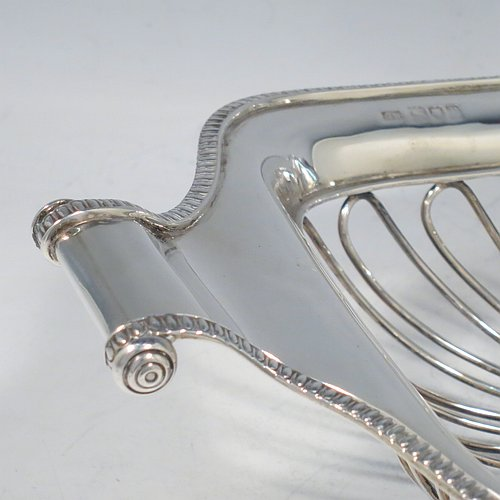 An Antique Sterling Silver table bread basket, having a rectangular shape with a wire-work body, an applied gadroon border, with two scroll side-handles, and sitting on a collet foot. Made by George Hancock of London in 1912. The dimensions of this fine hand-made antique silver bread basket are length 30.5 cms (12 inches), width 17 cms (6.75 inches), height 8 cms (3 inches), and it weighs approx. 527g (17 troy ounces).