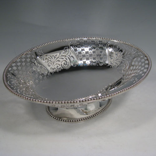 Antique Victorian sterling silver bread / fruit basket, having an oval body with hand-pierced geometrical and floral decoration, an applied cast bead border, two cast and hinged side-handles, and all sitting on a pedestal foot. Made by Edward and John Barnard of London in 1862. Length 34 cms (13.5 inches), width 26.5 cms (10.5 inches), height 11.5 cms (4.5 inches). Weight approx. 1,099g (35.5 troy ounces).