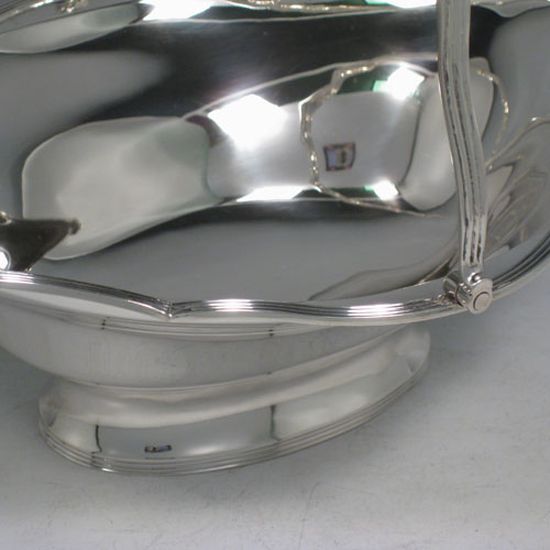 Antique Edwardian sterling silver table basket, having a plain oval body with shaped border and applied reeded edge, a hinged reeded handle, and sitting on a collet foot with reeded border. Made by Charles Stuart Harris of London in 1903. Height inc. handle 20 cms (8 inches), length 23 cms (9 inches), 19 cms (7.5 inches). Weight approx. 339g (11 troy ounces).