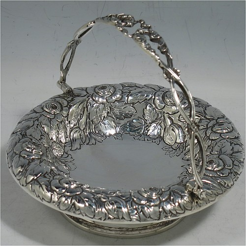 An Antique Victorian Sterling Silver sweet-meat basket, having a round body with hand-chased floral decoration, a hinged hand-pierced and chased swing handle, and all sitting on a plain round pedestal foot. Made by Henry Wilkinson & Co., of London in 1893. The dimensions of this fine hand-made antique silver basket are height 10 cms (4 inches), diameter 12.5 cms (5 inches), and it weighs approx. 147g (4.7 troy ounces).