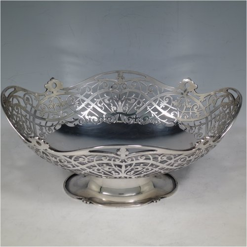 A Sterling Silver very pretty table basket, having an oval body with hand-pierced floral decoration, and sitting on a pedestal foot, with applied shaped borders. Made by Walker & Hall of Sheffield in 1929. The dimensions of this fine hand-made silver basket are length 24 cms (9.5 inches), width 17 cms (6.75 inches), height 11 cms (4.25 inches), and it weighs approx. 465g (15 troy ounces).