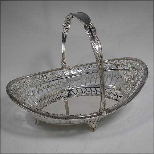 A very pretty Sterling Silver basket, having an oval body with an applied gadroon border, all hand-pierced with floral and scroll decoration, a hinged and pierced swing handle, and all sitting on four cast flange feet. Made by James Dixon and Sons of Sheffield in 1927. The dimensions of this fine hand-made silver basket are height 20 cms (8 inches), length 28 cms (11 inches), width 20 cms (8 inches), and it weighs approx. 548g (17.7 troy ounces).