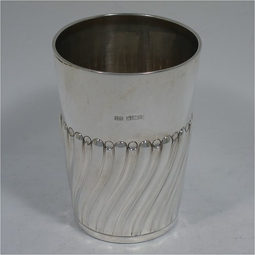 A very handsome Antique Edwardian Sterling Silver beaker, having a round straight-sided body with tapering sides, hand-chased work with half-swirl fluted decoration, with a gold-gilt interior, and all sitting on a flat base. Made by Henry Atkins of Sheffield in 1902. The dimensions of this fine hand-made antique silver beaker are height 10 cms (4 inches), diameter at top 7 cms (2.75 inches), and it weighs approx. 124g (4 troy ounces).