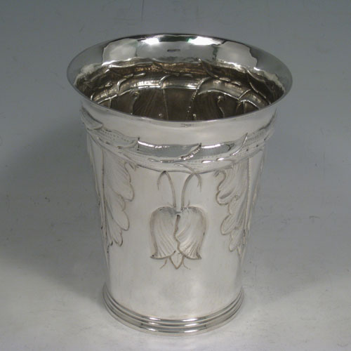 Brittannia standard silver Art Nouveau style beaker, having a round body with tapering sides, hand-chased floral decoration with tulips, and sitting on a collet foot. Made by S. J. Phillips of London in 1935, with extra Jubilee mark. The dimensions of this fine hand-made silver beaker are height 12 cms (4.75 inches), diameter at top 10 cms (4 inches), and it weighs approx. 244g (7.9 troy ounces).