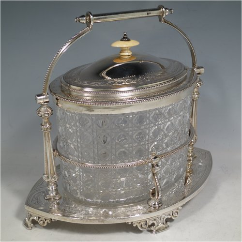 An Antique Victorian silver plated and cut crystal biscuit jar, having a hobnail cut oval crystal jar, a hand-engraved hinged lid with bead borders and an ivory finial, sitting in a bead-edged frame with swing handle, and an engraved floral base sitting on four cast foliate feet. Made in ca. 1880. The dimensions of this fine hand-made silver-plated and hand-cut crystal biscuit jar are height inc. handle 23 cms (9 inches), length of base 26 cms (10.25 inches), and width of base 17 cms (6.75 inches).