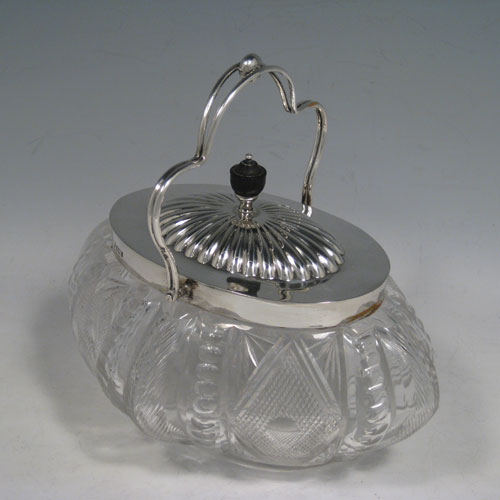 Antique Victorian sterling silver and hand-cut crystal biscuit jar, having an unusual oval crystal body with hand-cut floral and geometric work, a lift-off lid with half-fluting and wooden finial, and a wire-work swing handle. Made by Fordham and Faulkner of Sheffield in 1901. Height 18 cms (7 inches), length 20 cms (8 inches), width 15 cms (6 inches).