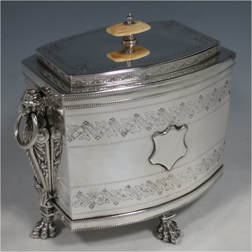 An Antique Victorian Silver Plated biscuit box, having a Neoclassical style rectangular shaped body with straight sides, applied bead-edged borders, with two bands of hand-engraving above and below a vacant cartouche, a hinged lid with ivory finial, two cast lion-mask ring handles, and all sitting on four cast lions-paw feet. Made in ca. 1880. The dimensions of this fine hand-made silver-plated biscuit boxr are height 18 cms (7 inches), length 21 cms (8.25 inches), and width 15 cms (6 inches).