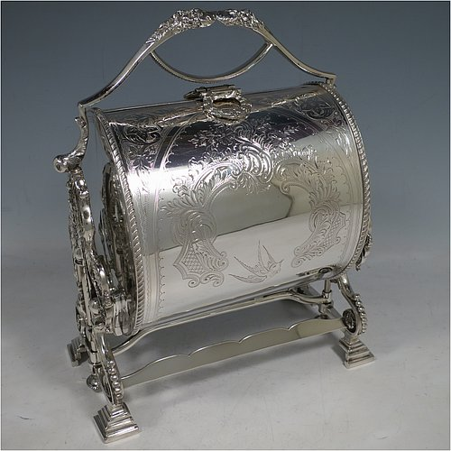 A very pretty Antique Victorian Silver Plated folding biscuit box, having an oval barrel-shaped body with beautiful hand-engraved floral and bird decoration, with straight sides and applied gadroon borders, sitting in a cast floral style mechanical frame with carrying handle, all sitting on four stepped feet, and with original gold-gilt interior with hand-pierced dividers. Made in ca. 1880. The dimensions of this fine hand-made silver-plated folding biscuit box are height 25.5 cms (10 inches), length fully opened 30.5 cms (12 inches), and width 20 cms (8 inches).