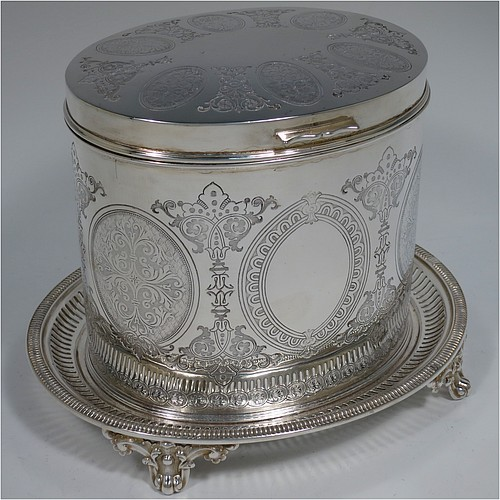 An Antique Victorian Silver Plated biscuit box, having an oval body with straight sides and very pretty hand-chased floral work, a hinged slightly domed lid with a thumb-piece, and all sitting on a hand-pierced attached plate with four cast foliate feet. Made by Roberts and Belk of Sheffield in ca. 1880. The dimensions of this fine hand-made antique silver-plated biscuit box are height 15 cms (6 inches), length 20 cms (8 inches), and width 17 cms (6.75 inches).