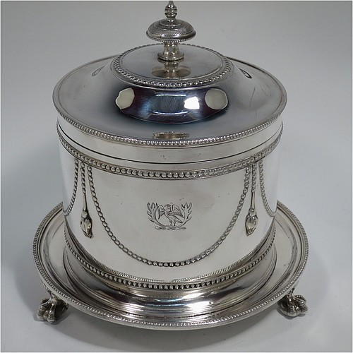 An Antique Victorian Silver Plated biscuit box, having a round body with applied bead-edged borders, straight sides and hand-chased swags of bead-work in a neoclassical style, a hinged domed lid with cast finial, and all sitting on an attached plate with three cast claw and ball feet. Made by James Thompson of Sheffield in ca. 1880. The dimensions of this fine hand-made antique silver-plated biscuit box are height 18 cms (7 inches), and diameter at base 18 cms (7 inches). Please note that this item is crested.