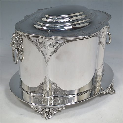 A large Antique Victorian Silver Plated biscuit box, having a Neoclassical style oval shaped body with straight sides, with bands of hand-engraving, a hinged domed lid, two cast lion-mask ring handles, and all sitting on an attached plate with four cast floral feet. Made in ca. 1880. The dimensions of this fine hand-made antique silver-plated biscuit box are height 16 cms (6.25 inches), length 23 cms (9 inches), and width 17 cms (6.75 inches).