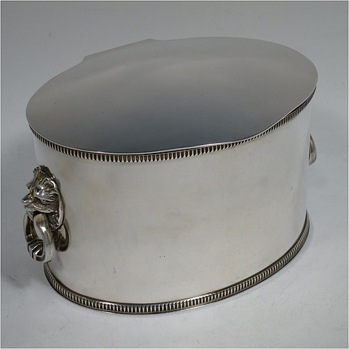 A very handsome Silver Plated biscuit box, having an oval body with straight sides and applied gadroon top and bottom borders, a hinged slightly domed lid with a thumb-piece, together with two cast lion-mask and ring side-handles, and all sitting flat base. Made by Rogers and Co., of Sheffield in ca. 1920. The dimensions of this fine hand-made silver-plated biscuit box are height 10 cms (4 inches), length 19 cms (7.5 inches), and width 13 cms (5 inches).