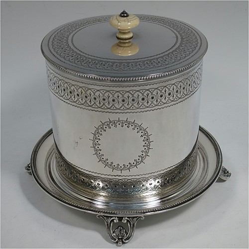 A very pretty Antique Victorian Silver Plated biscuit box, having a round body with straight sides and applied bead-edged borders, with very pretty hand-engraved bands of geometrical and floral work, a hinged flat lid with bone finial, and all sitting on an attached plate with four cast scroll and shell feet. Made by Elkington and Co., of Sheffield in ca. 1880. The dimensions of this fine hand-made antique silver-plated biscuit box are height 16 cms (6.3 inches), and diameter at base 18 cms (7 inches).
