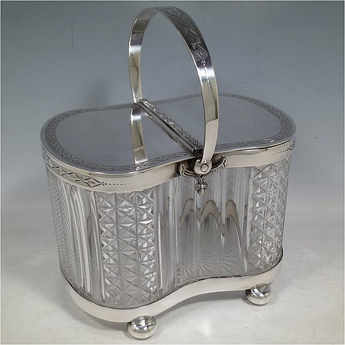 An Antique Victorian silver plated and cut crystal biscuit jar, having a hobnail and fluted cut  crystal body, a hand-engraved mechanically double-hinged lid with a swing handle, and all sitting on a base with four cushion feet. Made by Thomas Wilkinson & Sons of Sheffield in ca. 1890. The dimensions of this fine hand-made antique silver-plated and hand-cut crystal biscuit jar are height inc. handle 23 cms (9 inches), length of base 19 cms (7.5 inches), and width of base 14 cms (5.5 inches).