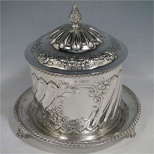 An Antique Victorian Sterling Silver biscuit box, having a round straight-sided body with hand-chased fluting and floral decoration, a hinged lid with cast foliate finial, and sitting on an attached base plate with a gadroon border and three cast foliate & lions-paw feet. Made by William Hutton & Sons of London in 1899. The dimensions of this fine hand-made antique silver biscuit box are height 18 cms (7 inches), diameter at base 19 cms (7.5 inches), and it weighs approx. 744g (24 troy ounces).