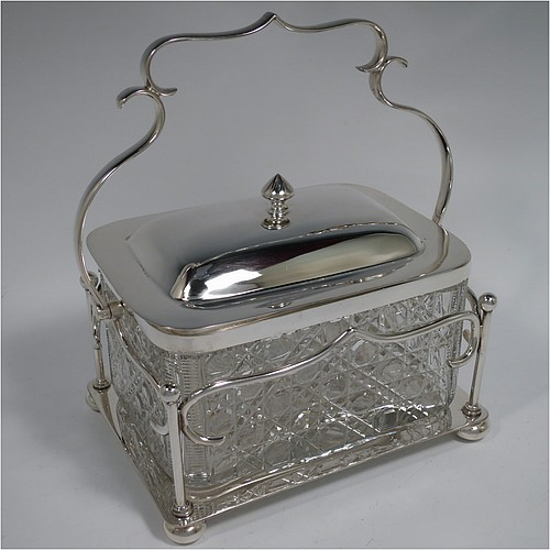 An Antique Victorian silver plated and cut crystal biscuit jar or box, having a hobnail cut rectangular crystal jar with straight sides, a plain lift-off lid with cast finial, all inside a galleried and scroll wire-work frame with swing handle, and sitting on a plain base with four cushion feet. Made by Walker and Hall of Sheffield in ca. 1880. The dimensions of this fine hand-made antique silver-plated and hand-cut crystal biscuit box or jar are height inc. handle 21.5 cms (8.5 inches), length 18.5 cms (7.25 inches), and width 13.5 cms (5.3 inches).