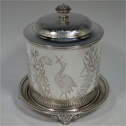 An Antique Victorian Silver Plated Chinoiserie style biscuit box, having a round body with straight sides and applied bead-edged borders, with very pretty hand-engraved flowers, reeds, birds, and butterfly work, a hinged domed lid with cast finial, and all sitting on a hand-pierced attached plate with four cast scroll feet. Made by the Atkin Brothers of Sheffield in ca. 1880. The dimensions of this fine hand-made antique silver-plated biscuit box are height 18 cms (7 inches), and diameter at base 17.5 cms (7 inches).