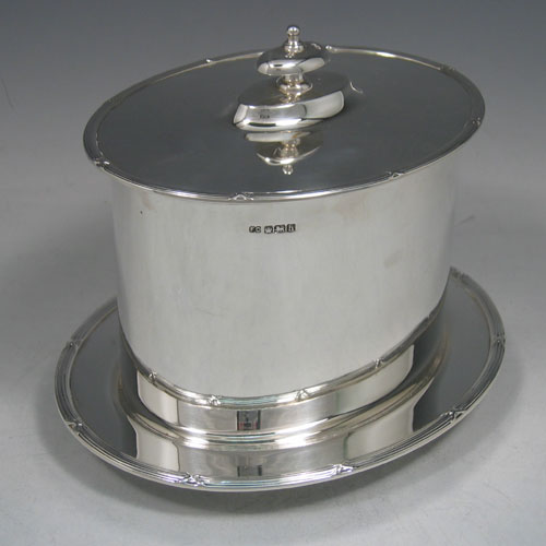 Sterling silver oval biscuit box with hinged lid and attached holding plate, with ribbon & reed border, made in Sheffield in 1925. Height 15 cms, width 20 cms.