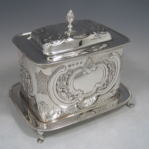 Sterling silver large hand-chased biscuit box with attached plate, made by William Hutton of Sheffield in 1930. Height 18 cms, width 21.5 cms, depth 16 cms. Weight 35 troy ounces.