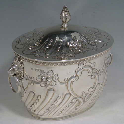 Antique Victorian sterling silver biscuit box, having an oval body with hand-chased fluting and floral decoration, hinged lid with finial, and two lion-mask ring handles. Height 18 cms (7 inches), length 18.5 cms (7.25 inches), width 13 cms (5 inches). Weight approx. 682g (22 troy ounces).