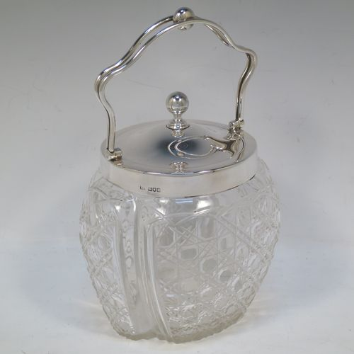A pretty Antique Edwardian Sterling Silver and hand-cut crystal biscuit jar, having an unusual crystal body with hand-cut hobnail pattern panels with fluted corners, a plain round lift-off lid with a ball finial, a wire-work swing handle, and all sitting on a star-cut flat base. Made by Robert Pringle of London in 1904. The dimensions of this fine hand-made antique silver and crystal biscuit jar are height (excluding handle) 15 cms (6 inches), length 15 cms (6 inches), and width 13 cms (5 inches).