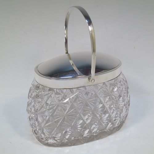 A very pretty and unusual Antique Victorian Sterling Silver and hand-cut crystal biscuit jar, having an oval crystal body with hand-cut hobnail and star-cut work, a plain oval mechanical lid which opens when moving the plain  hinged swing-handle either left or right, and all sitting on a flat star-cut base. Made by Heath and Middleton of Birmingham in 1899. The dimensions of this fine hand-made antique silver and crystal biscuit jar are height (excluding handle) 13 cms (5 inches), length 16.5 cms (6.5 inches), and width 9 cms (3.5 inches).