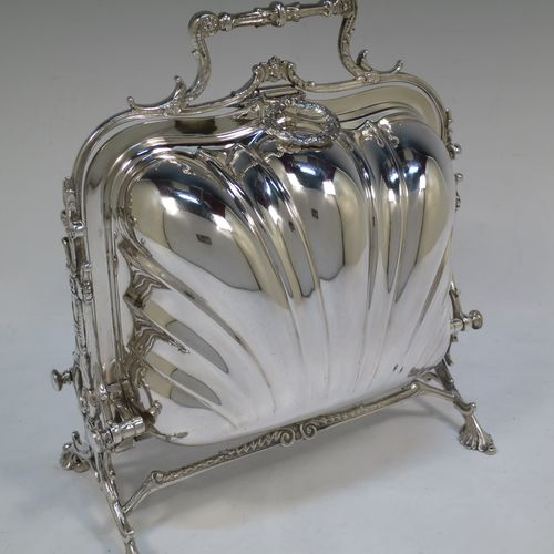 A very pretty Antique Victorian Silver Plated folding biscuit box, having a square shaped body with beautiful hand-chased fluting and rounded shoulders, sitting in a cast floral style mechanical frame with carrying handle and four shell feet, with original gold-gilt interior and  with hand-pierced dividers with scroll decoration. Made by the Fenton Brothers of Sheffield in ca. 1880. The dimensions of this fine hand-made antique silver-plated folding biscuit box are height 24 cms (9.5 inches), length fully opened 32 cms (12.5 inches), and width 22 cms (8.75 inches).