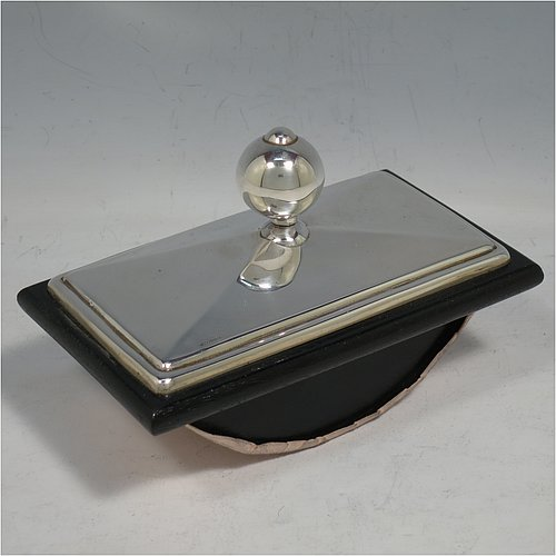 A Sterling Silver Rocker Blotter, having a very plain rectangular body with a panelled sloping surface, a black stained wooden rocker base, and a plain spherical handle that screws in to secure the rocker base and blotting paper to the upper body. Made in London in 1994. The dimensions of this fine hand-made silver rocker blotter are length 13.5 cms (5.25 inches), height 8.5 cms (3.3 inches), and width 7.5 cms (3 inches).