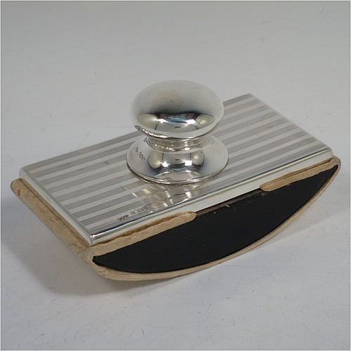 A Sterling Silver Rocker Blotter, having a rectangular body with engine-turned reeded decoration, a black stained wooden rocker base, and a plain round bellied handle that screws in to secure the rocker base and blotting paper to the upper body. Made by Wilmot Manufacturing Silversmiths of Birmingham in 1923. The dimensions of this fine hand-made silver rocker blotter are length 11.5 cms (4.5 inches), height 6.5 cms (2.5 inches), and width 6.5 cms (2.5 inches).