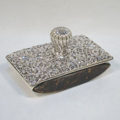 A very pretty Antique Edwardian Sterling Silver Rocker Blotter, having a rectangular body with rounded corners and hand-chased floral and scroll decoration, a leather covered rocker base, and a swirl fluted round handle that screws in to secure the rocker base and blotting paper to the upper body. Made by Henry Miller of Birmingham in 1902. The dimensions of this fine hand-made antique silver rocker blotter are length 11.5 cms (4.5 inches), height 6.5 cms (2.5 inches), and width 7 cms (2.75 inches).