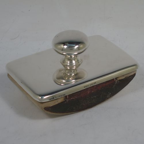 A handsome Antique Sterling Silver Rocker Blotter, having a very plain rectangular body with rounded corners, a leather covered rocker base, and a plain round handle that screws in to secure the rocker base and blotting paper to the upper body. Made by Stokes and Ireland of Chester in 1911. The dimensions of this fine hand-made antique silver rocker blotter are length 10 cms (4 inches), height 6 cms (2.3 inches), and width 6.5 cms (2.5 inches).