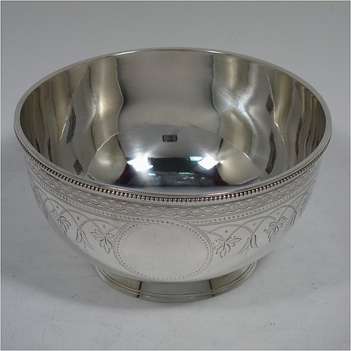 An Antique Victorian Sterling Silver bowl, having a round body, with an applied reeded border, with two vacant round cartouches on either side, all hand-engraved with floral and scroll-work decoration, and sitting on a collet foot with matching reed-work. Made by Edward Kerr Reid of London in 1877. The dimensions of this fine hand-made antique silver bowl are height 6 cms (2.25 inches), diameter 11 cms (4.3 inches), and it weighs approx. 147g (4.7 troy ounces).